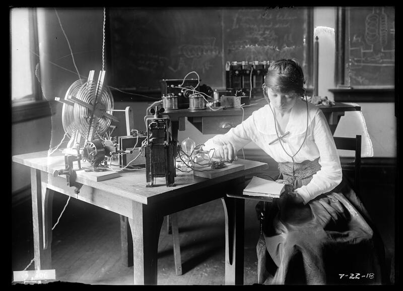 Woman seated at table with radio equipment, one of the instructors