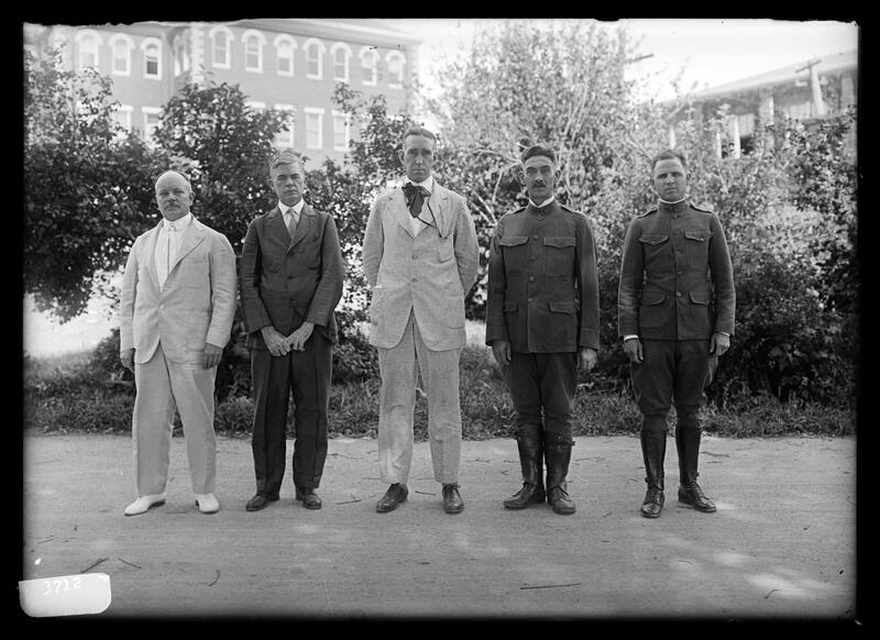 Five men with hats on, two military: Dean F. Paul Anderson, D. Howard Peak, President Frank L. McVey, Commandant H.N. Royden, Captain Harding
